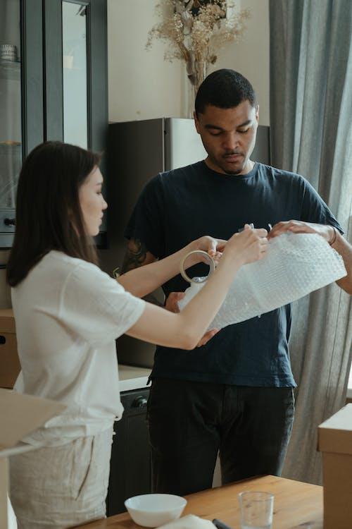 Man in Black Crew Neck T-shirt Holding White Tissue Paper