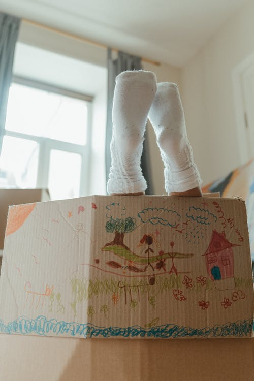 Person in White Pants and White Socks Standing Beside Brown Cardboard Box