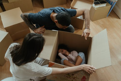 Man in Blue T-shirt and White Shorts Lying on Brown Cardboard Box