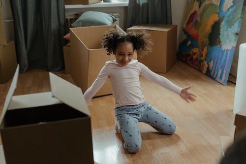 Girl in White Shirt and Blue Pants Lying on Floor