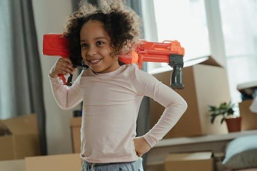 Girl in White Long Sleeve Shirt Holding Red Plastic Toy Gun