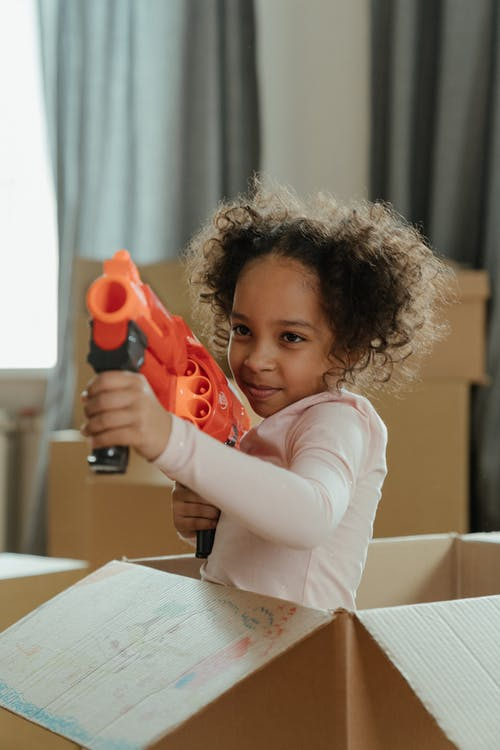 Child in White Long Sleeve Shirt Holding Orange and Black Toy Gun