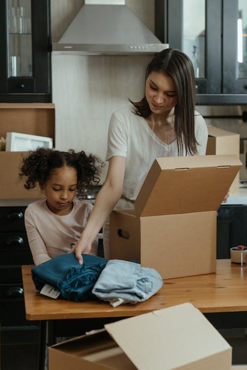 Girl in White Shirt Sitting on Brown Cardboard Box
