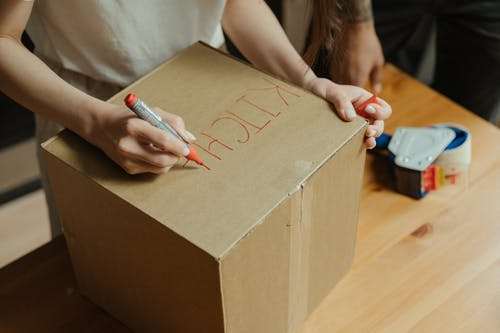 Woman in White Shirt Holding Red Pen Writing on Brown Cardboard Box