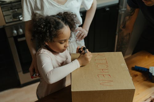 Girl in White Long Sleeve Shirt Writing on Brown Paper