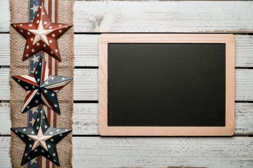 Top view of chalkboard in wooden frame placed on lumber table near tape with US flag and star badges