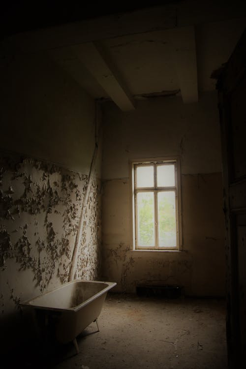 Interior of abandoned room with shabby walls and old bathtub placed in front of window