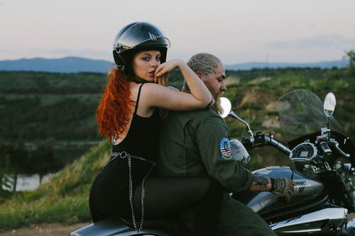 Side view of sensual young female with foxy hair in helmet sitting on motorcycle behind brutal tattooed boyfriend during ride in highland