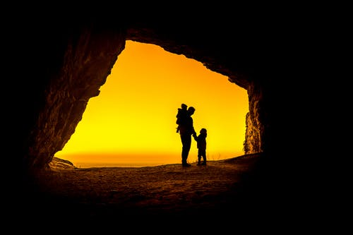 Silhouette of 2 Person Standing on Rock Formation during Sunset