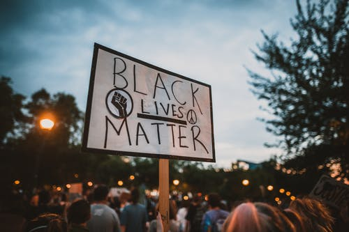 From below of anonymous female holding sign with black lives matter inscription during anti racism campaign against cloudy sky