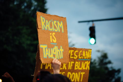 Unrecognizable demonstrators showing anti racism placards during protest