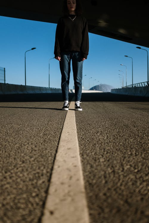 Person in Black Pants and White Sneakers Standing on Gray Asphalt Road