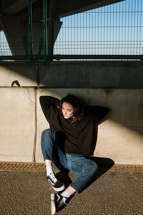 Woman in Black Long Sleeve Shirt and Blue Denim Jeans Sitting on Brown Concrete Wall during