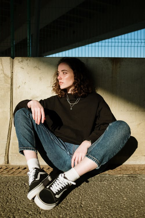 Woman in Black Long Sleeve Shirt and Blue Denim Jeans Sitting on Brown Wooden Bench