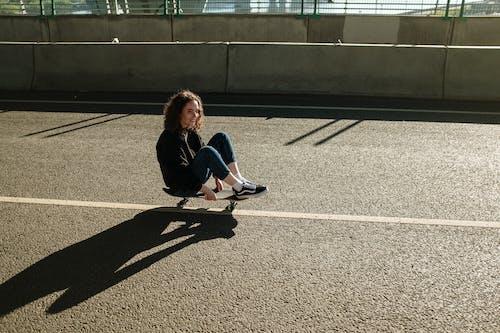 Woman in Black Jacket Sitting on Gray Concrete Floor