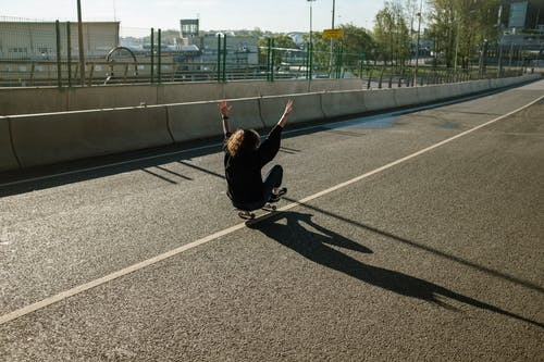Man in Black Jacket and Black Pants Jumping on Gray Asphalt Road