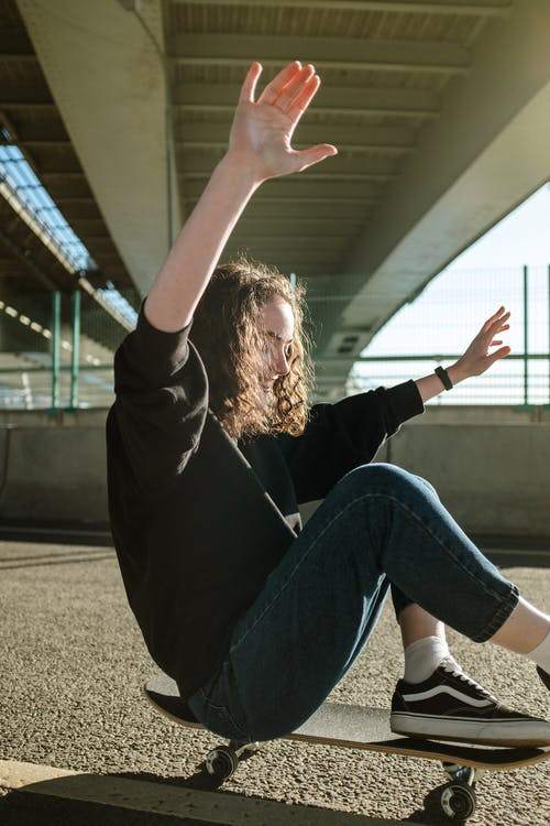 Woman in Black Long Sleeve Shirt and Blue Denim Jeans Sitting on Concrete Floor