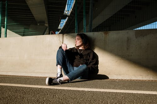 Woman in Black Jacket and Blue Denim Jeans Sitting on Gray Concrete Floor