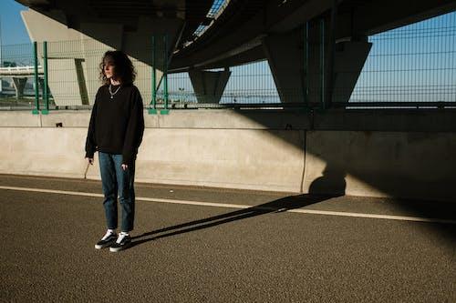 Man in Black Jacket Standing on Black Metal Frame