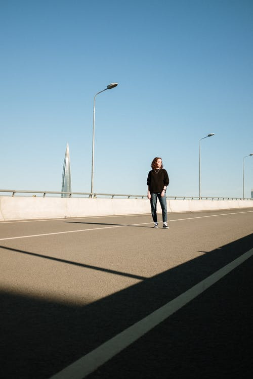 Man in Black Jacket and Black Pants Walking on Gray Concrete Road