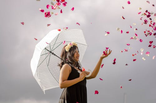 Positive young ethnic woman throwing flower petals against cloudy sky