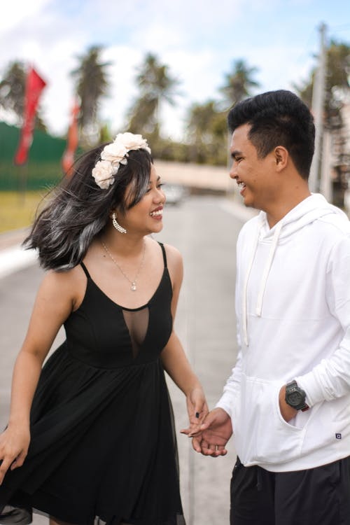 Happy young ethnic female in black dress standing on street with boyfriend and laughing on sunny day
