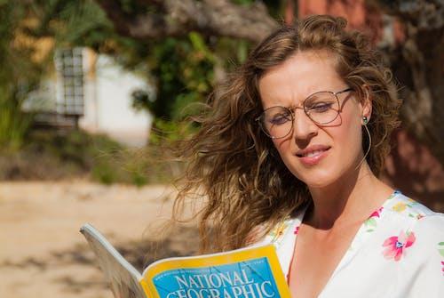 Woman Wearing Eyeglasses Reading a Magazine