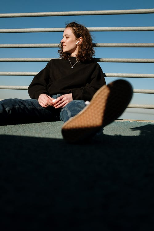 Woman in Black Jacket and Blue Denim Jeans Sitting on Bench