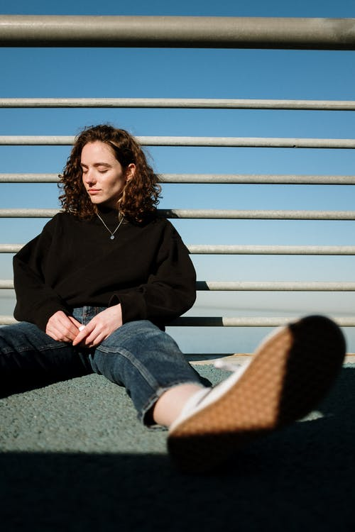 Woman in Black Long Sleeve Shirt and Blue Denim Jeans Sitting on White Bench