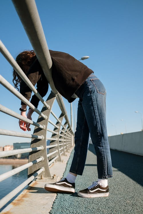 Woman in Blue Denim Jeans and Brown Jacket Standing on White Metal Railings