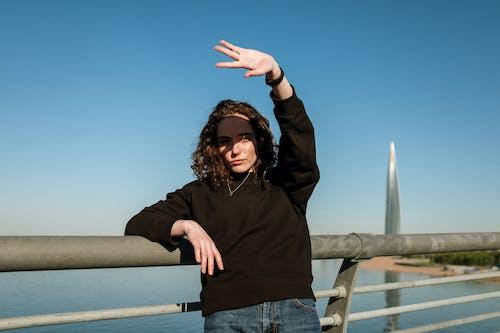 Woman in Black Hoodie Standing on Bridge