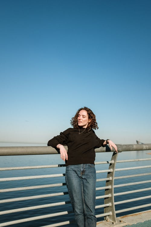 Woman in Black Long Sleeve Shirt and Blue Denim Jeans Standing on Brown Wooden Dock during