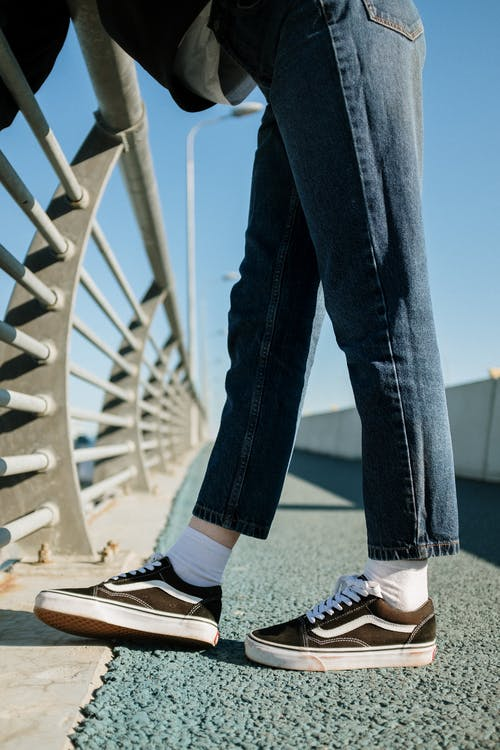 Person in Blue Denim Jeans and Black and White Sneakers Standing on White Metal Bridge