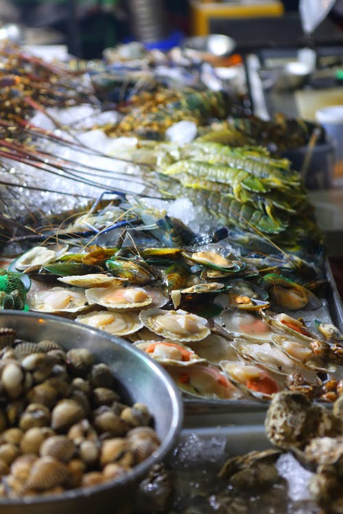 High angle pile of assorted fresh healthy raw seafood placed on stall of traditional market