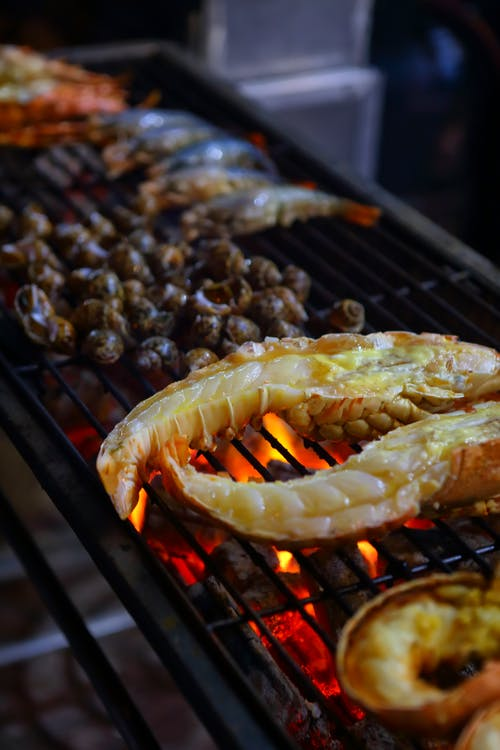 High angle of fresh tasty lobsters placed on metal grid of grill with various seafood in traditional restaurant