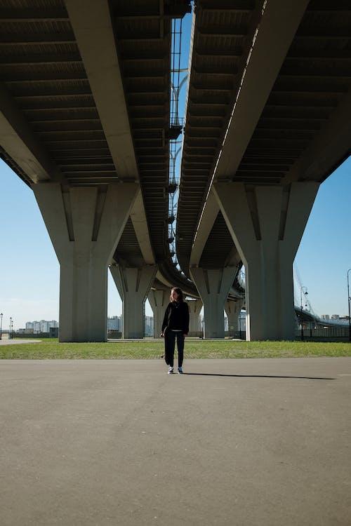 Person in Black Jacket and Black Pants Walking Under White Bridge