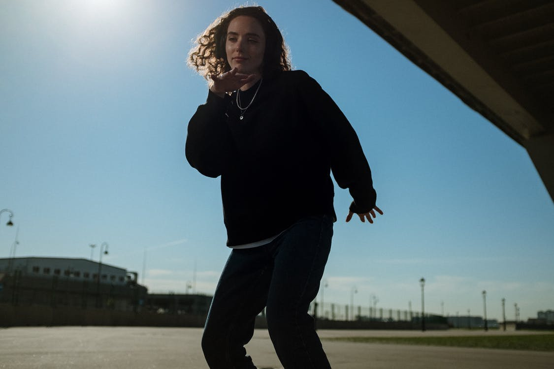 Woman in Black Long Sleeve Shirt and Black Pants Standing on Gray Concrete Floor