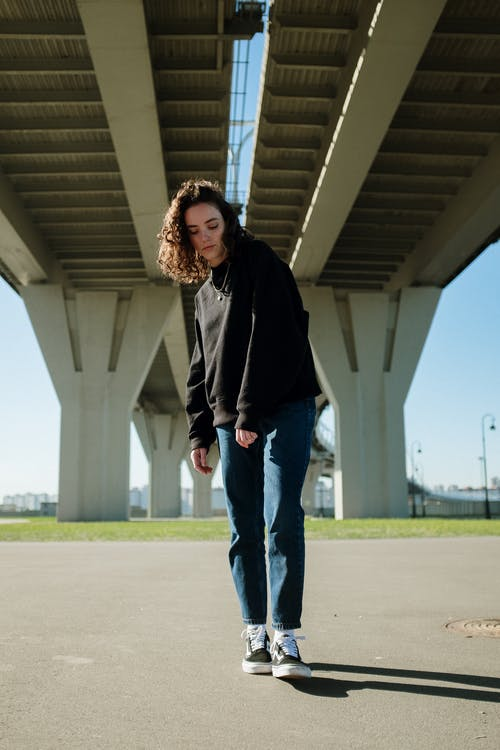 Woman in Black Jacket Standing Under Bridge