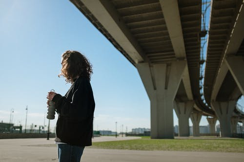 Woman in Black Jacket and Blue Denim Jeans Standing Under Bridge