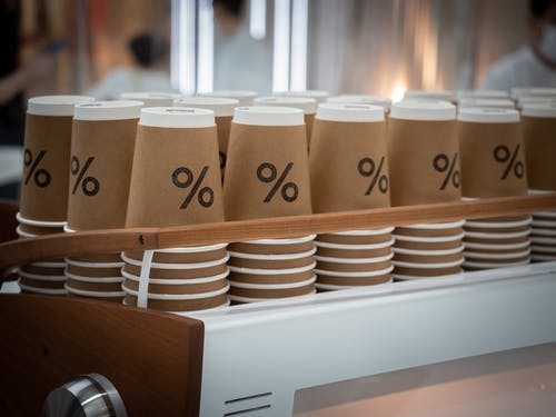 Stack of similar disposable cups with printed percent sign placed on counter in modern coffee shop