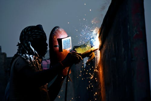 Anonymous black male welder working with torch on street