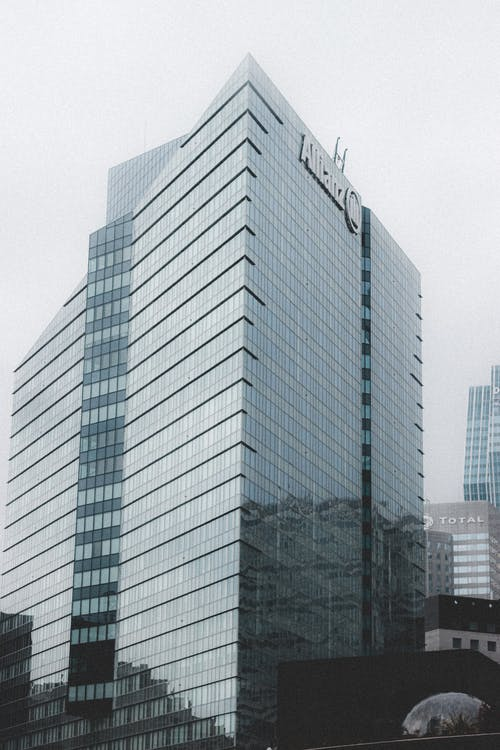 Corner of majestic glossy multi storey office building with transparent windows in daylight