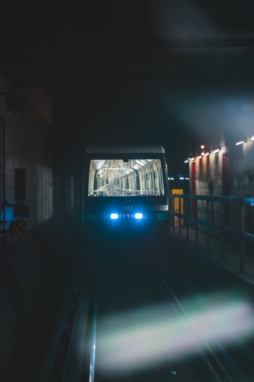 Empty subway car with blue turned on glowing headlamps on rails between wall and fence