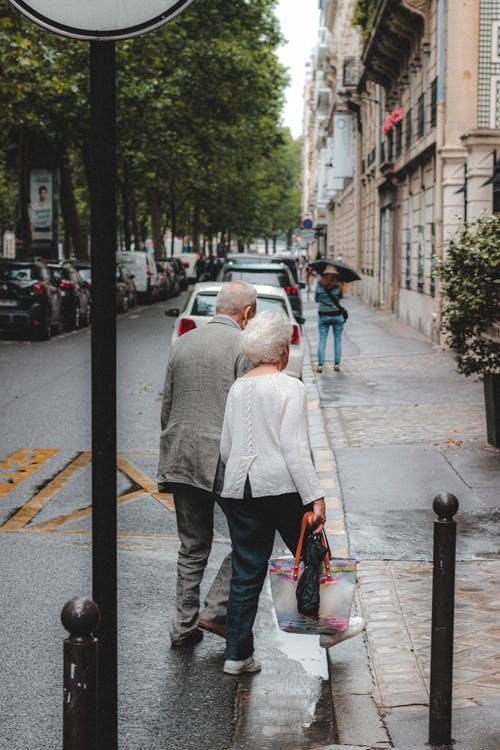 Full body back view senior couple in formal wear walking across asphalt road surrounded by buildings and parked automobiles