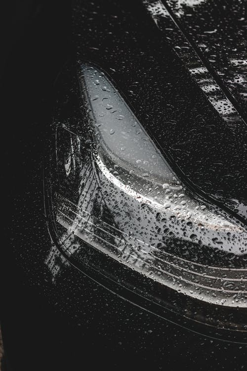 Black and white of round tiny transparent drops of rain on surface of headlamps and bumper of contemporary luxury car