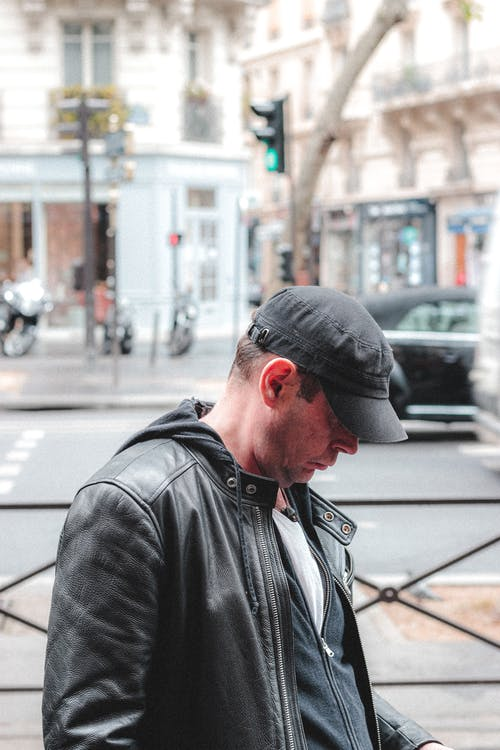 Side view of unrecognizable thoughtful adult male in black leather coat and hat looking down in street near zebra crossing in daylight