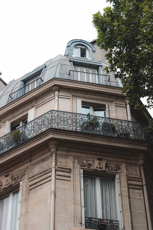 Exterior of old beige construction with balconies decorated with wrought iron fences and pot plants
