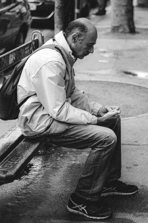 Side view of pensive aged man in casual clothes with backpack sitting on wooden bench at street in big city and looking down