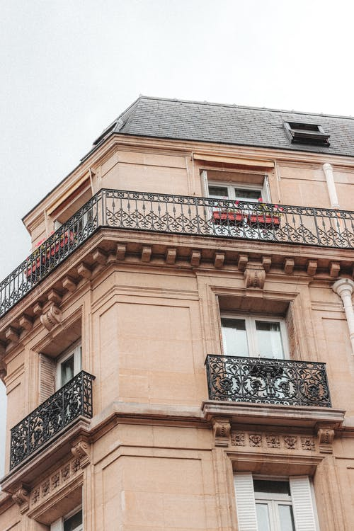 Low angle of building with balconies and ornamental columns in residential area of town in cloudy day