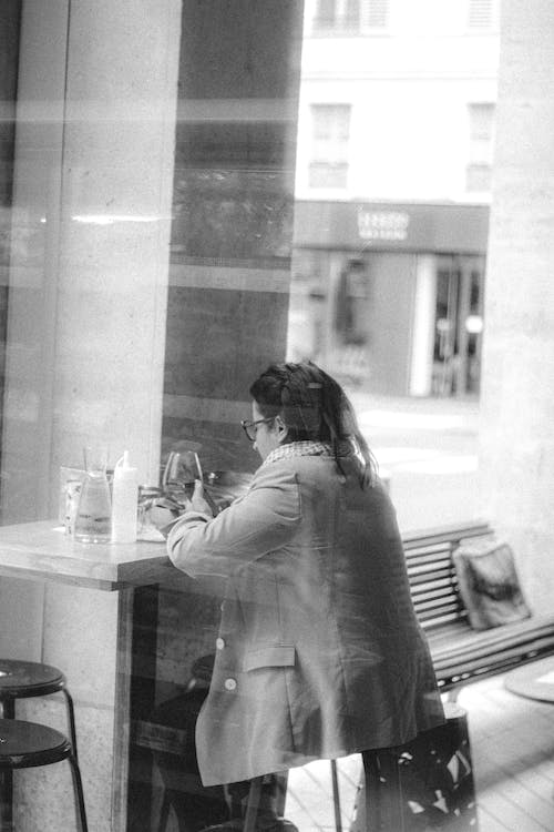 Anonymous woman chatting on smartphone in cafe